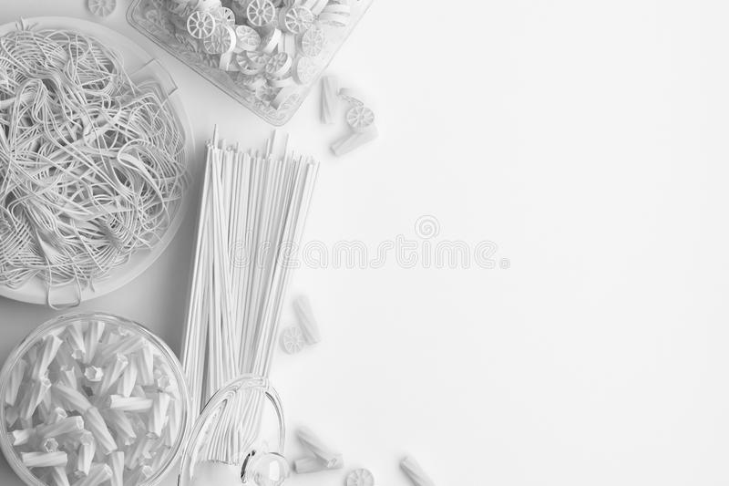 Monochrome composition of dry and boiled pasta and spaghetti on a white background. Banner with copy space for text. A set of food. On the top view. 3D vector illustration