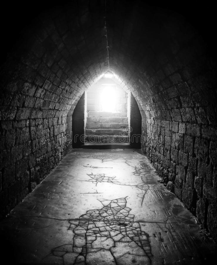Monochrome dark image of an old underground pedestrian foot tunnel with an arched roofs stone walls and a cracked floor with a stock photos