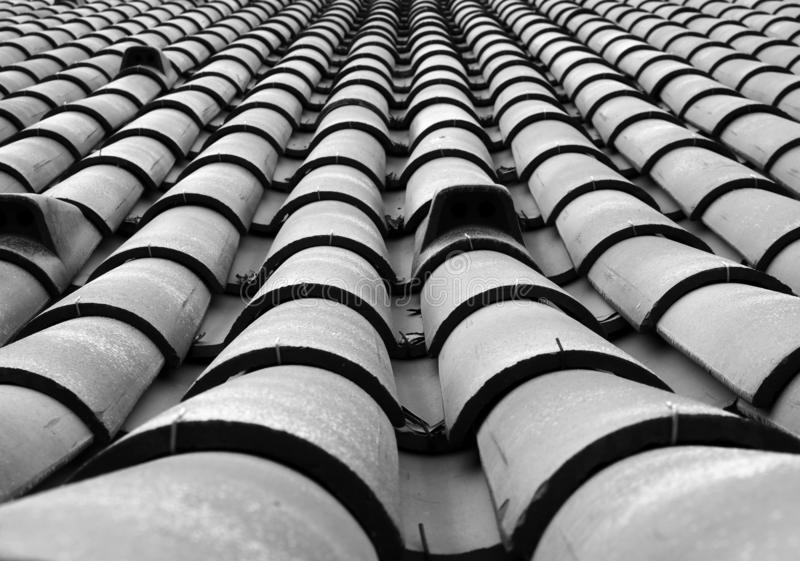 Monochrome full frame diminishing perspective view of an old roof with curved tiles in lines with ventilation slots royalty free stock images