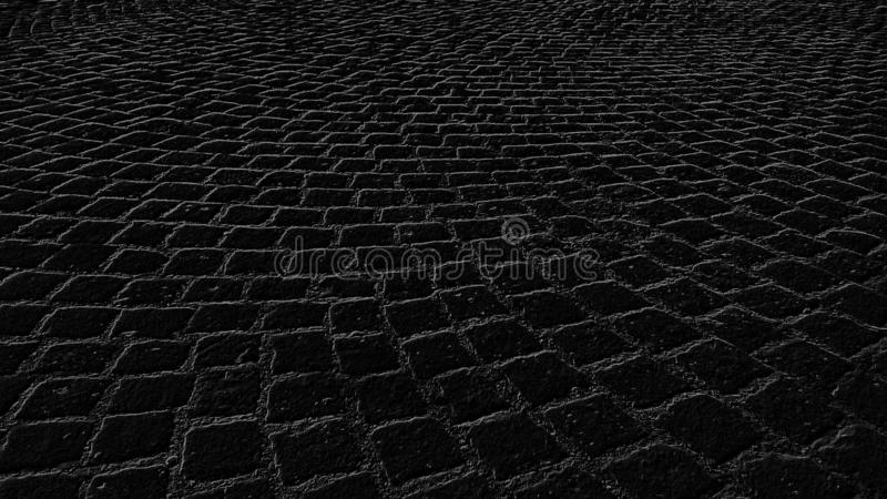 Monochrome graphic drawing of paving stones in an ancient square in the old city. Black background with gray pattern. A square-. Paved road in the old district stock images
