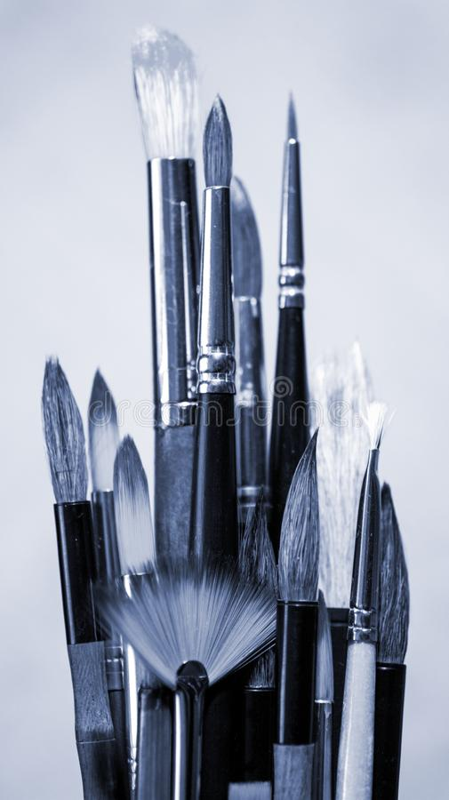 Monochrome image of art brushes of different sizes and shapes. Monochrome image of art brushes of different sizes and shapes on light background. Vertical stock photos