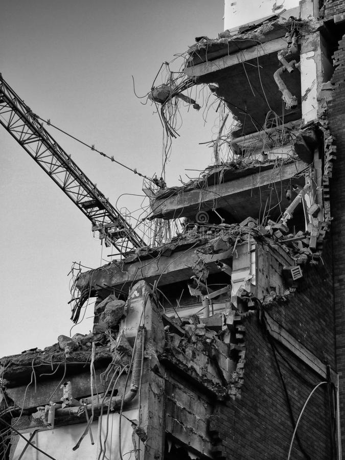 Monochrome image of a building being demolished showing construction crane. A monochrome image of a building being demolished showing construction crane stock photo