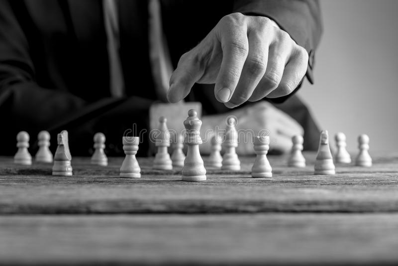 Monochrome image of a businessman wearing suit playing chess stock photos