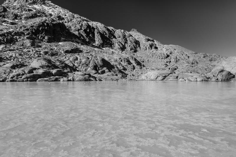 Monochrome image of frozen lake and rocky mountains in Spain, Gredos royalty free stock photos