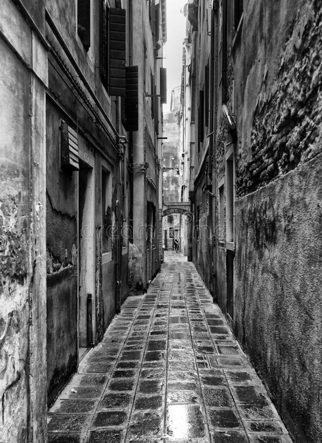 Monochrome image of a long narrow urban alley with wet cobbles and old eroded walls in venice italy. A monochrome image of a long narrow urban alley with wet stock images