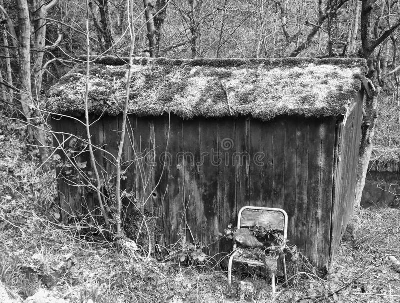 Monochrome image of an old abandoned wooden shack in woodland with broken chair outside and moss covered roof. A monochrome image of an old abandoned wooden royalty free stock image