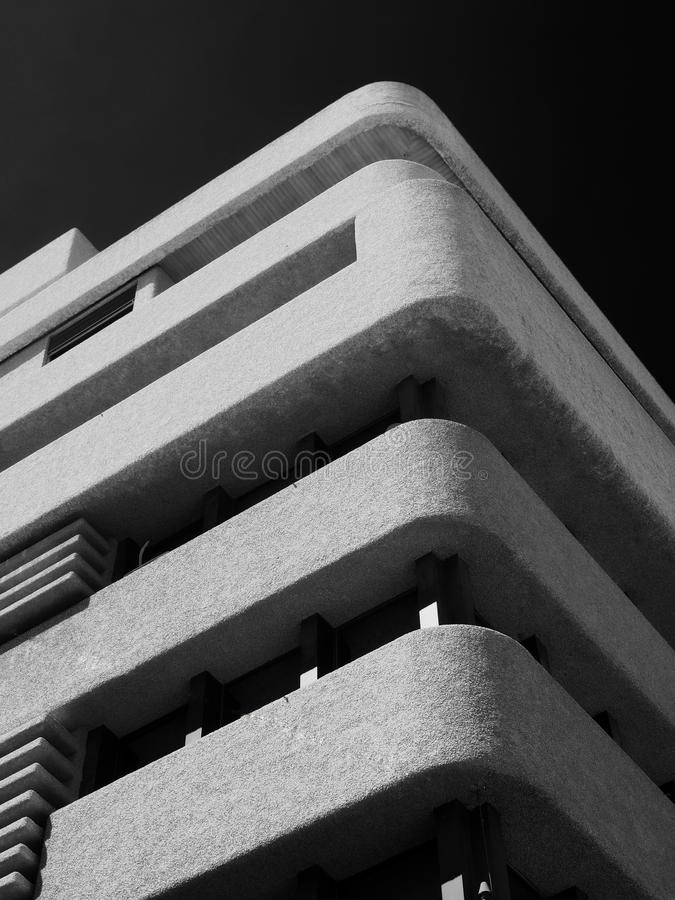 Monochrome image of an old brutalist concrete tower block with rounded textured corners against a dark sky royalty free stock photo