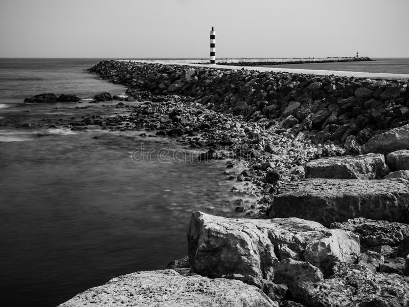 Old lighthouse in Algarve, in a curve walkway stock photo