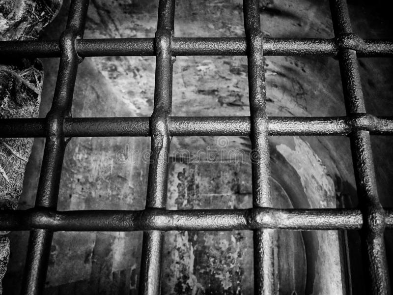 Monochrome image old metal prison type bars on a dark old empty cell like space stock photo