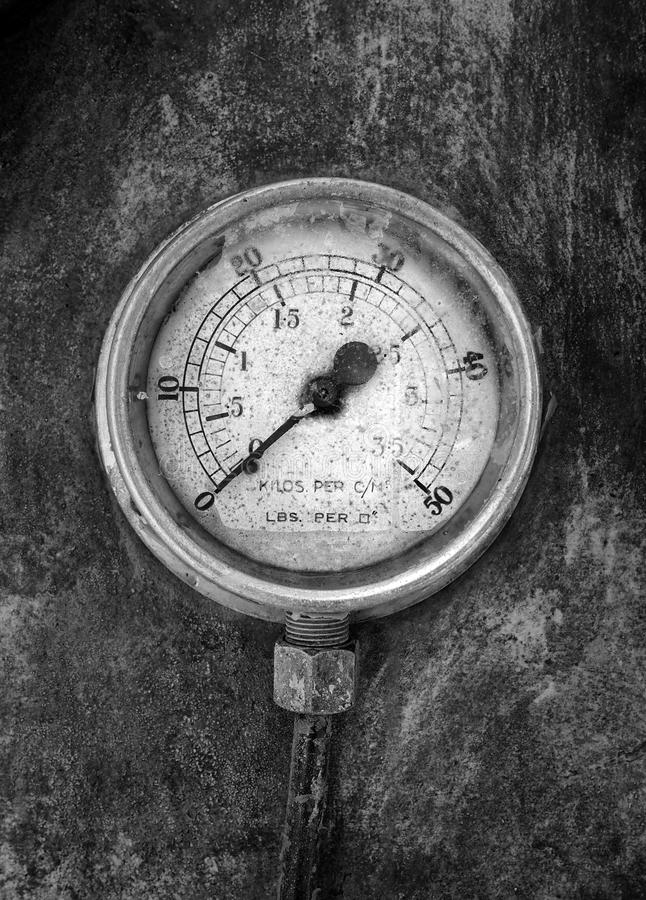 Monochrome image of an round industrial pressure gauge with numbers round the dial mounted on a metal surface. Of a large abandoned diesel powered generator stock photography