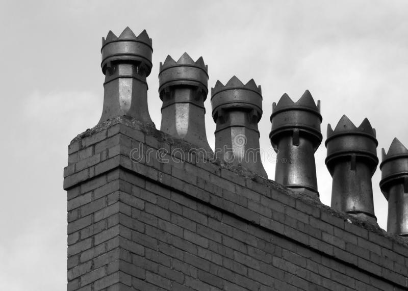 Monochrome image of a row old fashioned chimney pots on a brick built house royalty free stock image