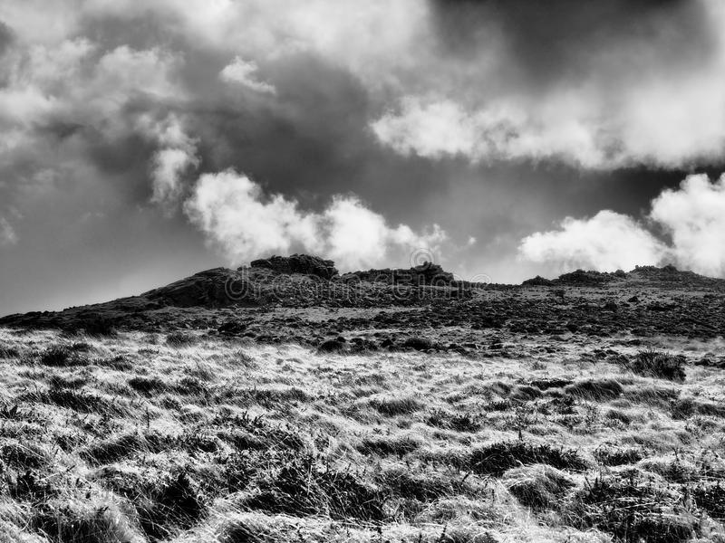 Monochrome image of rugged rocky outcrop tor on moorland hill with dark clouds rolling over, Dartmoor. National Park, Devon, UK stock images