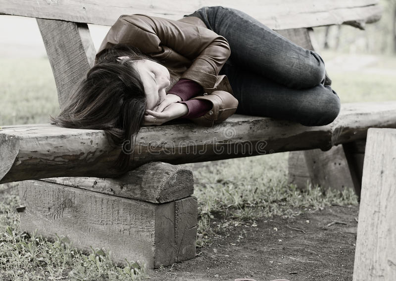 Monochrome image of a woman on a park bench royalty free stock photography