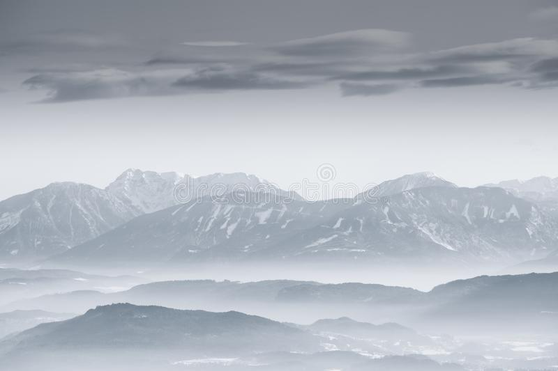 A monochrome mountain landscape in winter with snow and fog in the valley on a calm morning stock photo
