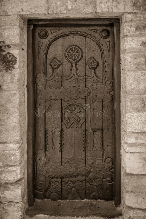 Monochrome old carved door on a stone bulding and big hindges royalty free stock photos