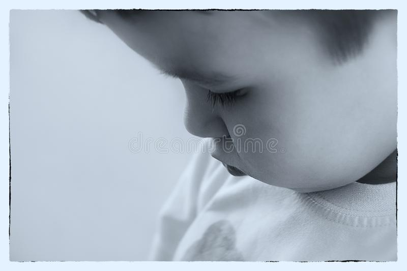 Monochrome old style photo of little boy who looking down. Conceptual Monochrome old style photo of little boy who looking down. Close up portrait royalty free stock photo
