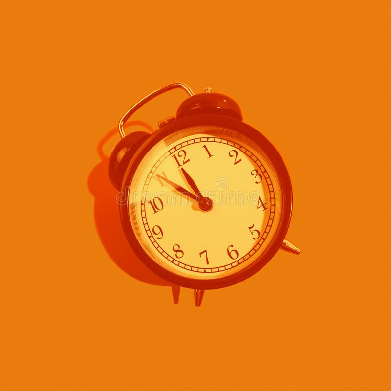 Monochrome orange classic style alarm clock isolated on background. New Year and start up concept stock photography