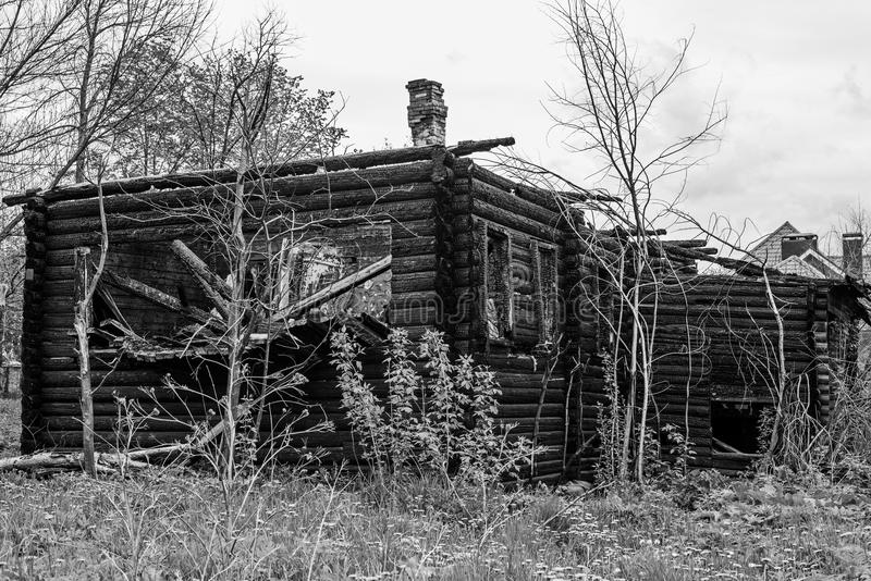 Black and white photo of the abandoned remains of a burnt down wooden building royalty free stock image
