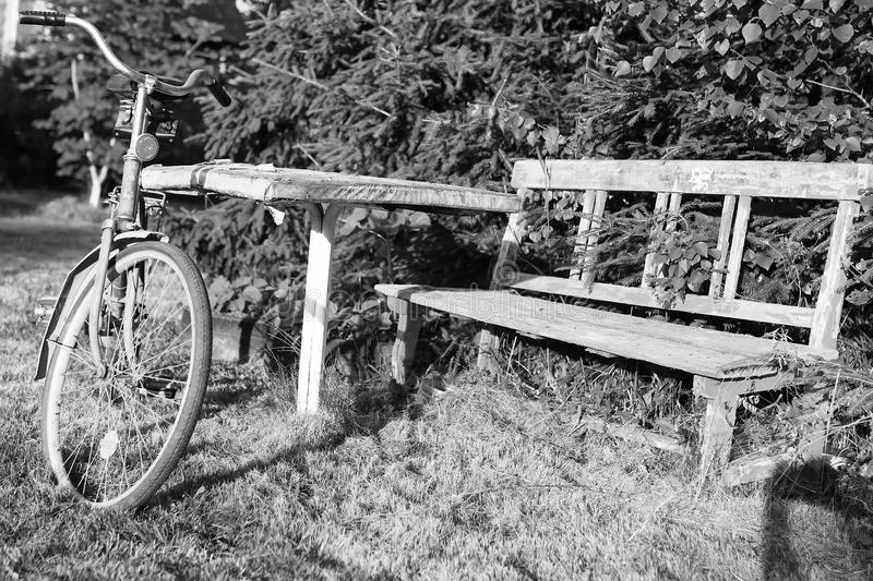 Monochrome photo bicycle on a rural nature. Old shabby two-wheeled bicycle parked on the lawn near the house stock photos