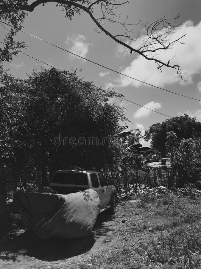 Monochrome photo of old broken pick-up under the hars sunlight. Monochrome photo of old broken pick-up covered with cloth under harsh sunlight in Dominican stock photos