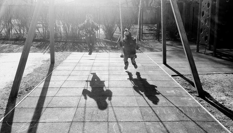 Monochrome Photography of Children On Swing royalty free stock photography