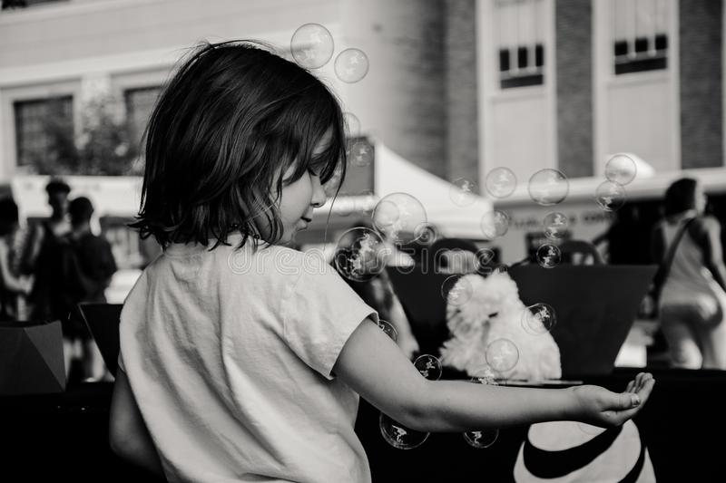 Monochrome Photography of Girl Playing With Bubbles stock image