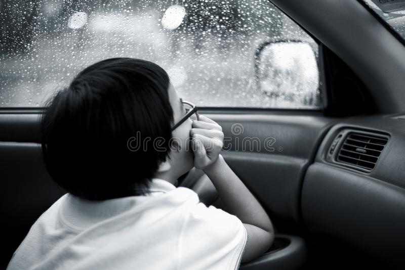 Monochrome portrait Asian girl sits in the car and looks out of window watching the rain and droplets royalty free stock images