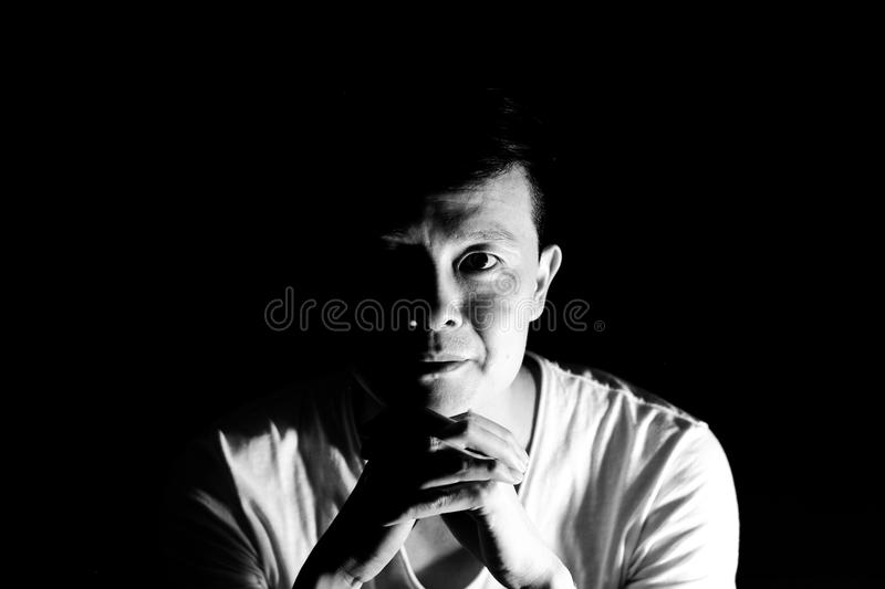 Monochrome portrait of asian man looking at the camera with isolated black background stock images