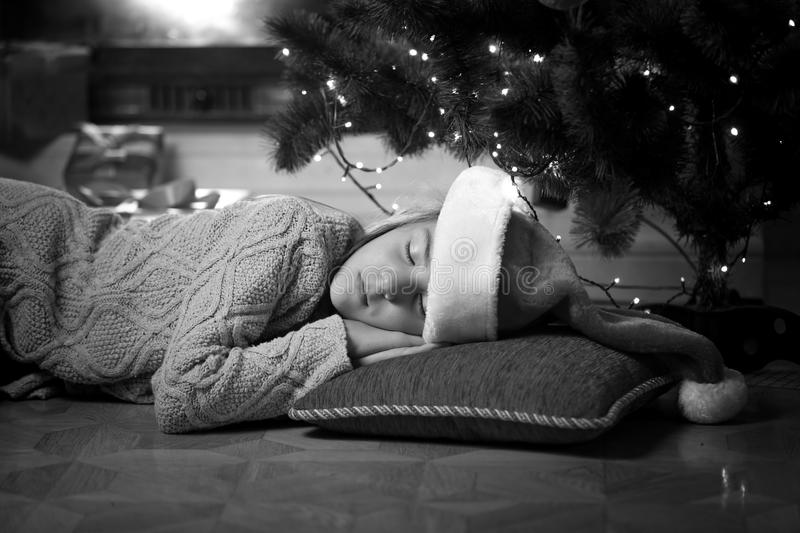 Monochrome portrait of cute girl sleeping under Christmas tree royalty free stock image