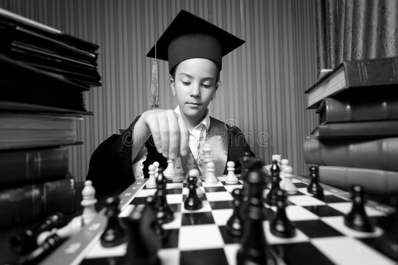 Monochrome portrait of girl graduation hat playing chess. Black and white portrait of girl graduation hat playing chess stock photography