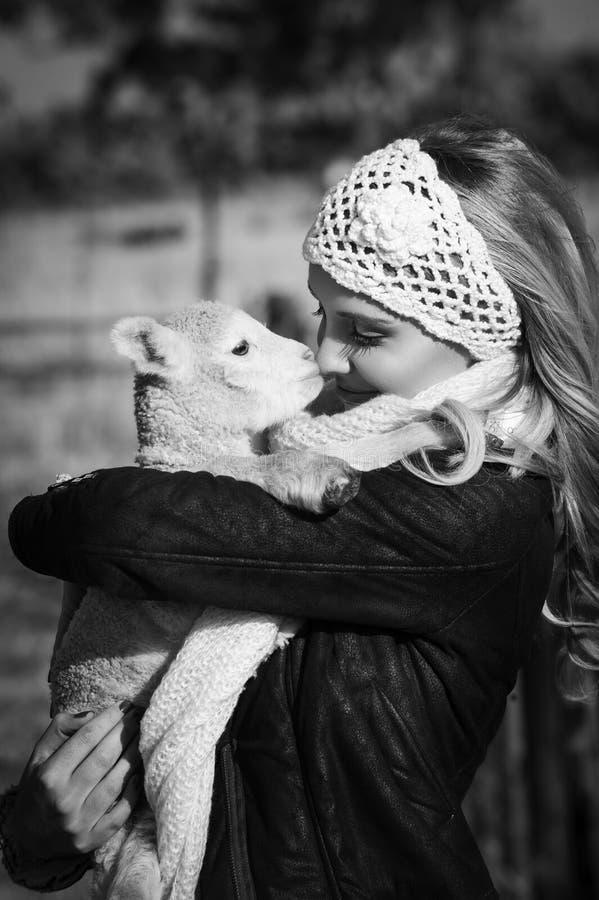 Monochrome portrait of woman cuddling little lamb stock photography