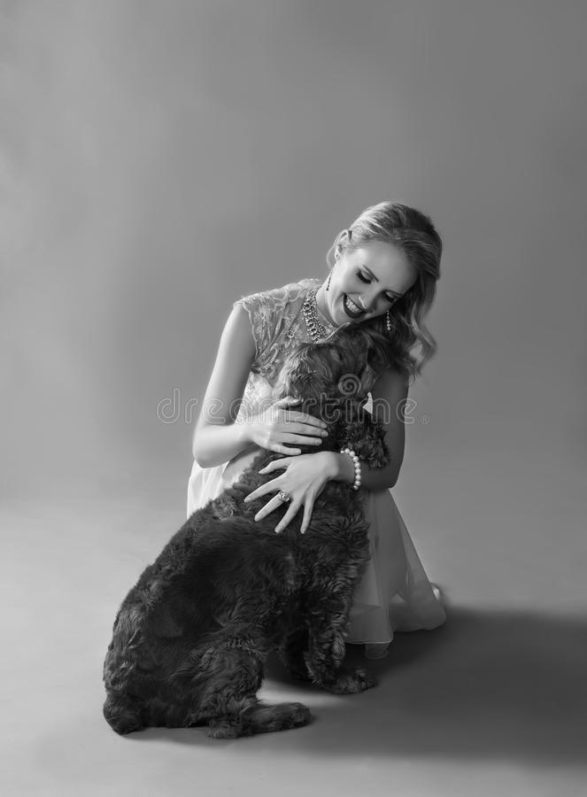 Monochrome portrait of woman playing with dog royalty free stock photo
