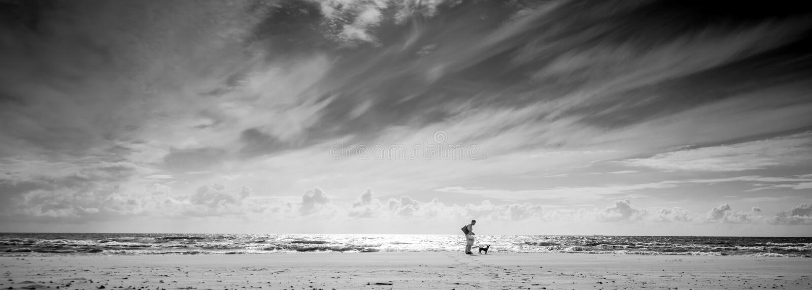 Monochrome sea shore landscape. Of sand sea and sky. woman with dog standing royalty free stock photography