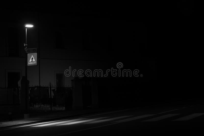 Monochrome shot of a street lamp, which illuminates the pedestrian crossing at night royalty free stock photos