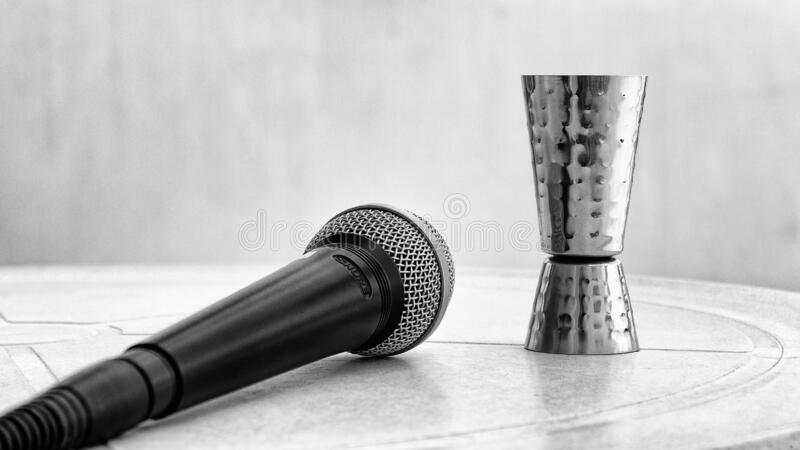 Still-life shot of a mic & shot glass placed on a table. A monochrome still-life shot of a mic & shot glass placed on a table stock images