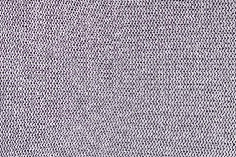 Monochrome texture of knitting. Beautiful background with loops. The knitted garment is pale purple. Monochrome texture of knitting. Beautiful blank background stock images