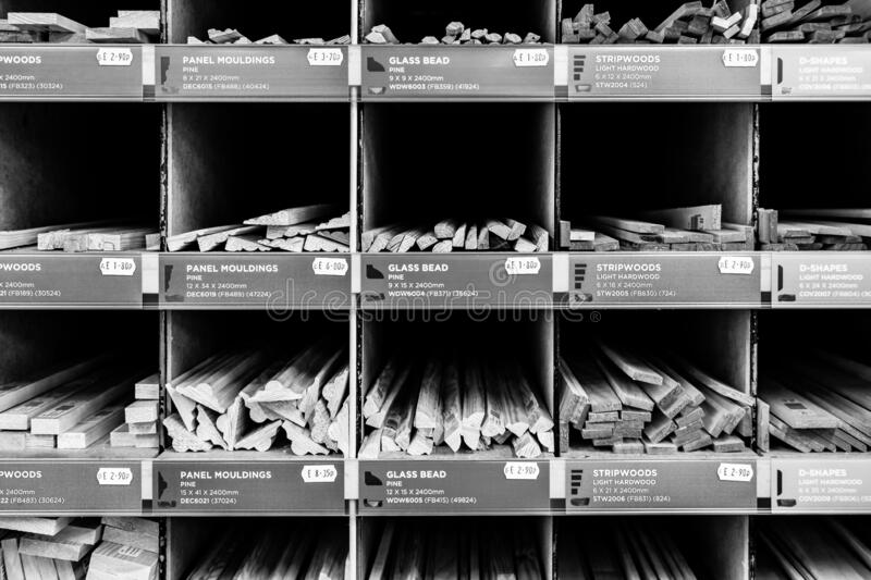 Monochrome view of a selection of timber strips of various designs and lengths seen in there specific compartments. stock photography
