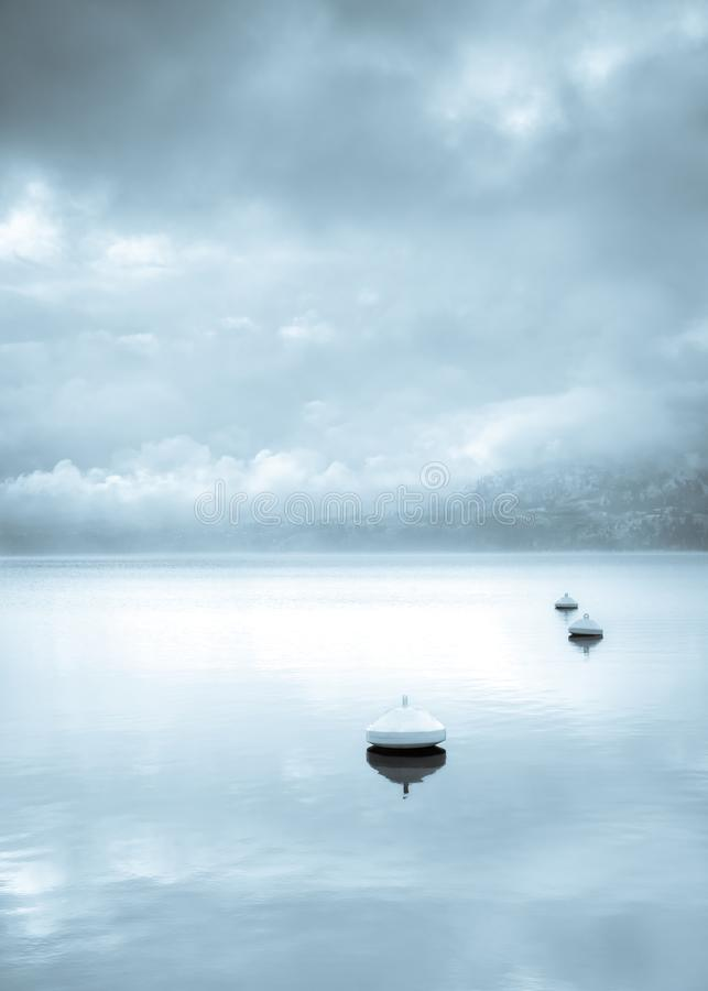 Monochromu krajobraz pociesza unosić się w spokojnym jeziorze z wodą odbija zimy burzy mgłę z górą w odległości i chmury zdjęcie royalty free