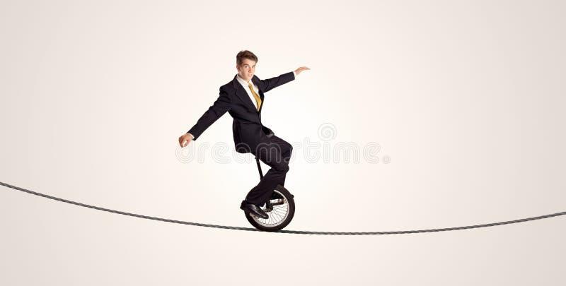 Monociclo estremo di guida dell'uomo di affari su una corda immagine stock