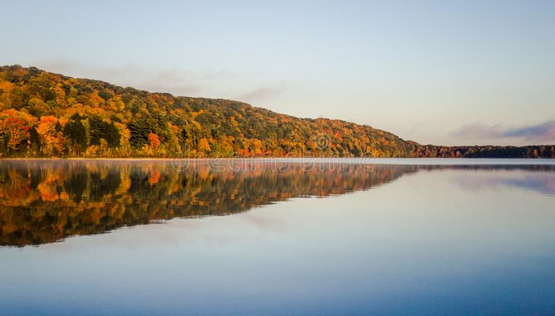 Michigan Autumn Wilderness Lake Reflections. Monocle Lake in northern Michigan with autumn foliage reflected in the calm blue water of the lake and a sunset stock photos