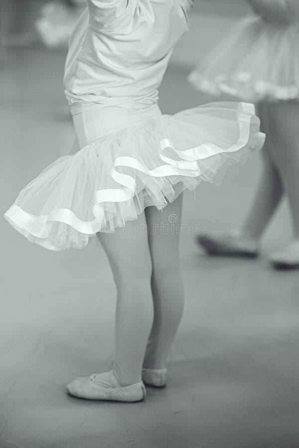 Monocromio - studenti di balletto del bambino in poco tutu rosa con il nastro del raso, il body e l'involucro rosa di balletto fotografia stock