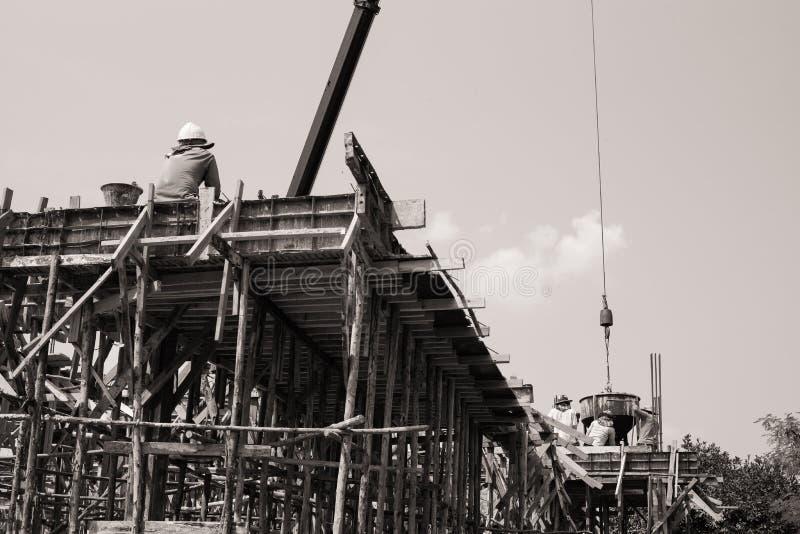 Monocromo de los trabajadores que llevan el envase del cemento para verter en s foto de archivo libre de regalías