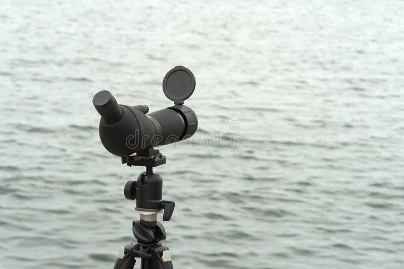 Monocular Birdwatching do espaço da mancha em um tripé perto da água fotos de stock royalty free