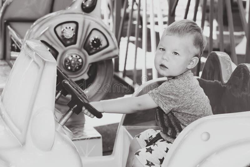 Monokrom bild av pysen som kör leksakbarnbilen royaltyfri foto