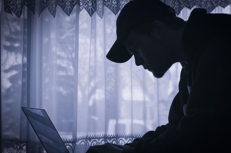 Monokrom konturbild av en ung man på hans bärbar dator royaltyfria foton
