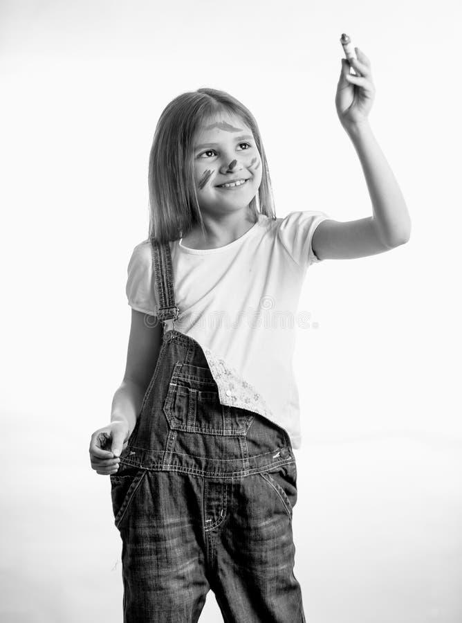 Monokrom stående av att le flickateckningen vid målarfärgröret royaltyfri bild