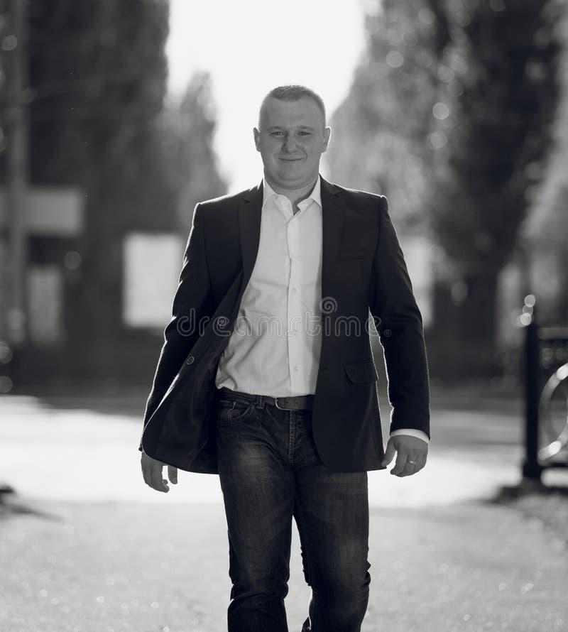 Monokrom stående av den stiliga mannen i dräkt som går på gatan arkivbild