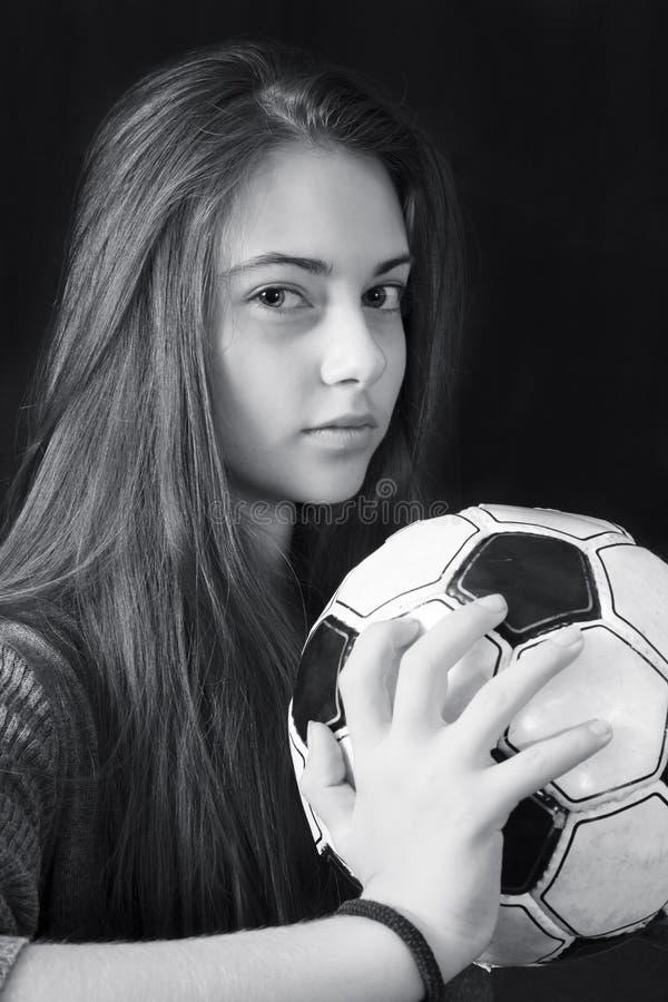Monokrom stående av den unga härliga flickan med fotbollbollen royaltyfria foton