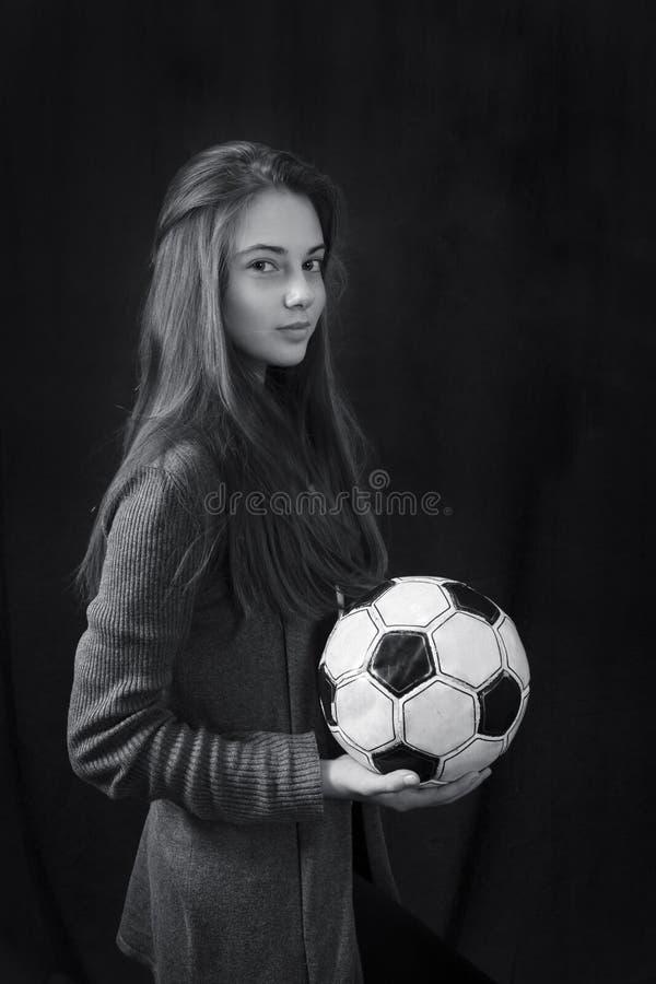 Monokrom stående av den unga härliga flickan med fotbollbollen royaltyfri bild