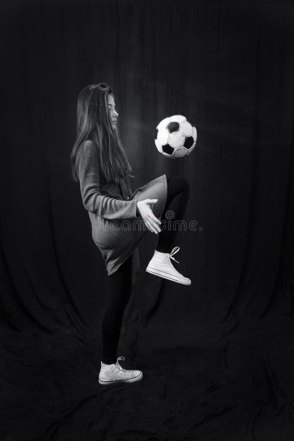 Monokrom stående av den unga härliga flickan med fotbollbollen royaltyfri foto